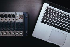 Mischpult liegt neben einem Macbook