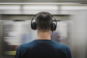 Mann mit Kopfhörern steht vor einem durchfahrenden Zug