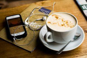 Smartphone mit Kopfhörern liegt neben einer Tasse Cappuccino