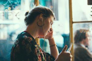 Frau mit Kopfhörern schaut auf ihe Smartphone