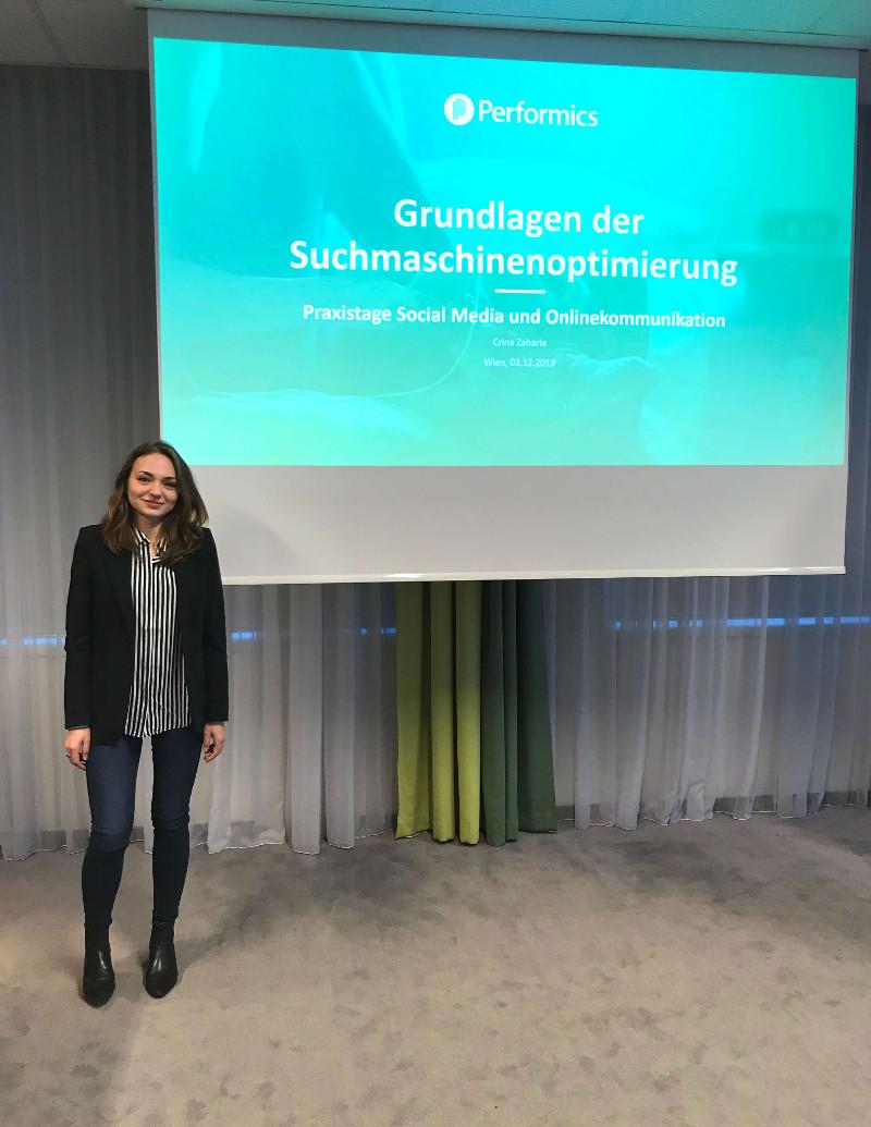 """Foto von Performics Junior Managerin Crina Zaharia vor der Titelfolie ihres Workshops """"Grundlagen der Suchmaschinenoptimierung"""" auf den SCM Praxistagen in Wien."""