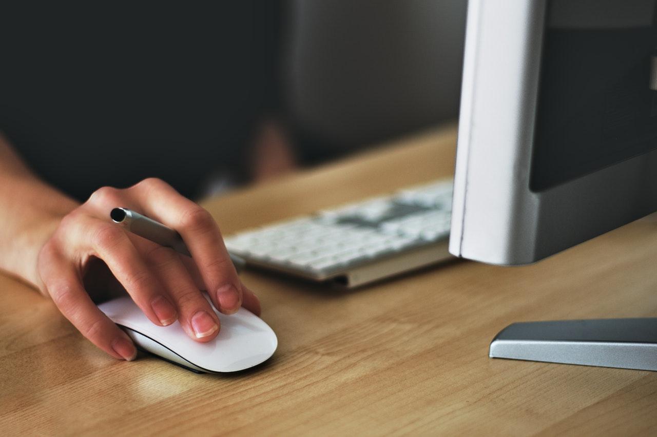 Die Hand einer Computernutzerin auf einer Maus